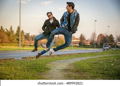 Pair of Young Men Leaping into Air and Clicking Heels Together in Unison While Walking on Path in Urban Park Alongside Paved Road at Sunset