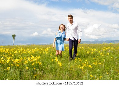 pair of young people running around the field with flowers