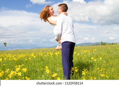 pair of young people walk among wildflowers