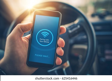 Pairing Smartphone with Car Multimedia Audio System. Using Mobile Phone Device While Driving. Hands Free Talking and Listening Online Music While Traveling by Car.