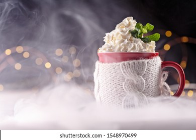 pairs of cups, light bulbs on the background. wooden table, red mug. winter theme. smoke