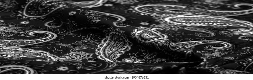 Paisley black-white pattern on a black background. decorated the bandanas of cowboys and bikers popularized by The Beatles, ushered in the era of hippies and became the emblem of rock and roll.