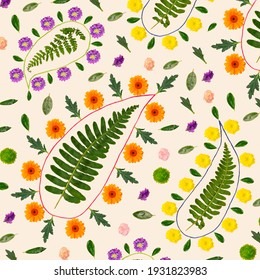 Paisley inspired floral pattern. Arrangement created from fresh colorful natural flowers, green leaves and strings. Top view against beige color.
