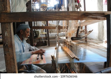 PAITHAN, MAHARASHTRA, INDIA, 25  MARCH 2016 : Unidentified Indian man weaving traditional paithani saree on handloom, paithani saree is famous for hand woven traditional sarees.