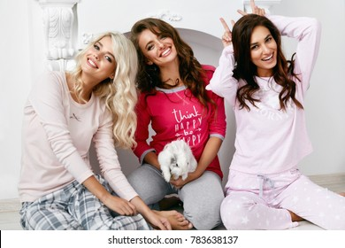 Pajama Party. Female Models In Night Clothing Having Fun. Beautiful Happy Young Women In Stylish Sleepwear Playing With Rabbit And Spending Time Together At Sleepover Home Party. High Resolution.