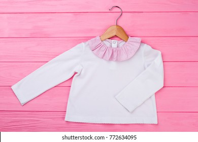 Pajama top for little girl. White garment with pink ruffle collar on wooden  hanger. 18dc30f41