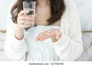 In pajamas, a Japanese woman drinking morning of medicine