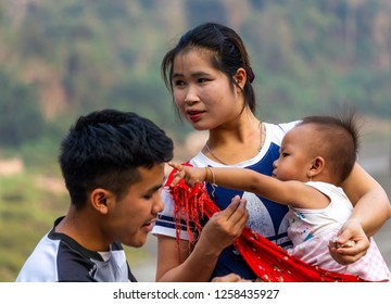 Pak Beng, Laos - April 3, 2018: Portrait of a local family with a child near the Mekong river in a remote area of Laos