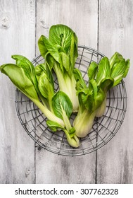 pak choi in metallic basket on white wooden background, top view