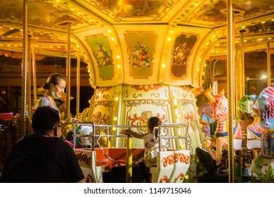 Pak Kret, Nonthaburi, Thailand. - On August 4, 2018 - Family playing Carousel Horse at night.