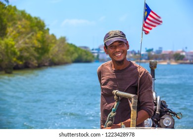 Pak Nam Krabi river, Krabi Town, Thailand - Februrary 2014. Portrait of a taxi boat driver with a beard, cap and brown jacket, smiling and looking at the camera, Malaysian flag developing behind back.