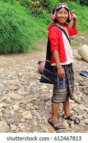 Pak Nam Noy, Laos-October 8, 2015: The Akha Ya-Er hill tribe are an ethnic minority living in the area between E.Myanmar-N.Thailand-W.Laos-S.China. Woman waits to cross by row-boat the Nam Phak river.