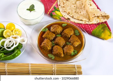 Pakistani Food, Kofta salan, Spicy indian curry, Delicious meatballs with salad, bread, yogurt and colourful cushion on white background.