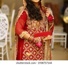 Pakistani Indian Bridal getting ready. Bridal wearing red wedding dress and jewelry  Karachi, Pakistan, 01 January 2021
