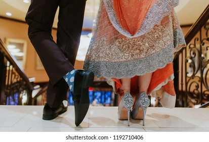 Pakistani Indian bride and groom showing wedding shoe and sandals