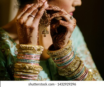 Pakistani Indian bride putting gold  earrings and showing wedding bangles jewelry Lahore, Pakistan 15, June, 2019