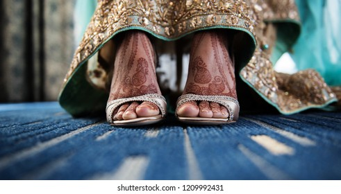 Pakistani Indian  bride putting her wedding sandals shoes