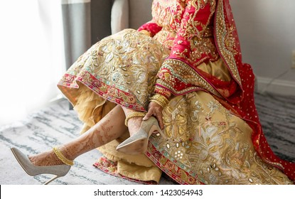 Pakistani Indian bride showing Feet mehndi design and wearing wedding sandals with anklet jewelry