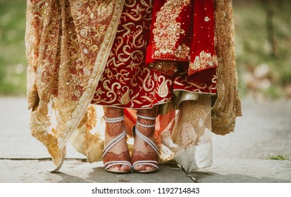Pakistani Indian bride showing foot mehndi design and wedding lehenga and sandals