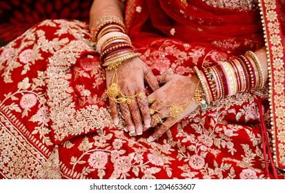 Pakistani Indian bride showing hands mehndi design or gold jewelry and wedding Lehenga sharara embroidery design