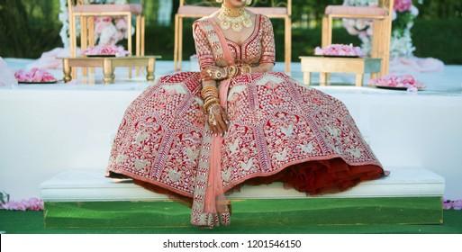 Pakistani Indian bride showing red lehenga and wedding jewelry