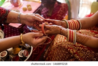 Pakistani Indian Bridesmaids Putting Bangles on Bride hand