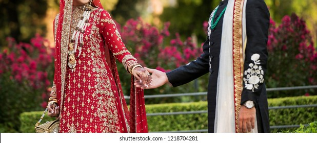 Pakistani Indian lovebirds holding hands and bridal putting wedding purse