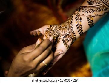 Pakistani Indian mehndi artist making henna design bridal hands