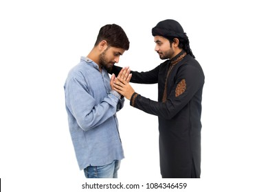 Pakistani Muslim boy apologizing upset angry brother. boy asking brother for forgiveness. Brother trying to convince brother. Conflicted brothers in studio on white background. Relationship problem.