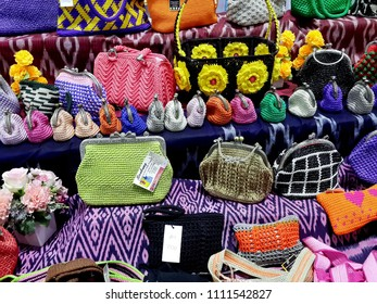 PAKKRET, NONTHABURI, THAILAND - JUNE 12, 2018: Aparticipant to an OTOP fair displays colourful purses and bags  at Impact Challenger on June 12, 2018 in Pakkret, Nonthaburi, Thailand.