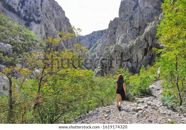 The Paklenica karst river canyon, a national park in Croatia.Northern Dalmatia, on the southern slopes of Velebit mountain. Velika (Big) Paklenica. Young girl/tourist hiking. Summer sunny weather.