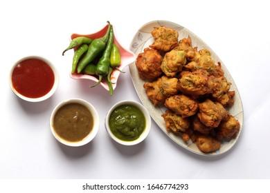 Pakoda Snacks with Tomato Ketchup and Chutni or Sauces   Indian or Pakistani Basin Pakora and Meat or Qeema Samosa, Potato Samosay Snacks are the best Ramadan iftar Meal of the World. - Shutterstock ID 1646774293