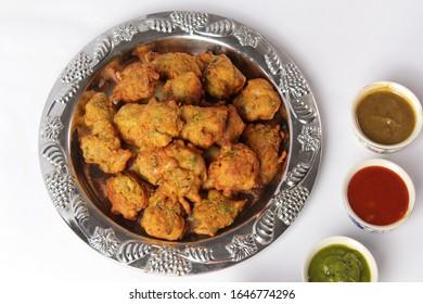 Pakoda Snacks with Tomato Ketchup and Chutni or Sauces   Indian or Pakistani Basin Pakora and Meat or Qeema Samosa, Potato Samosay Snacks are the best Ramadan iftar Meal of the World. - Shutterstock ID 1646774296