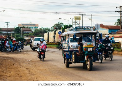 Pakse, Champasak Province, Laos- 15 December 2016: Sunset on a main highway - road through Pakse to the city of Paksong. Traffic. Lao people ride on motorbikes.