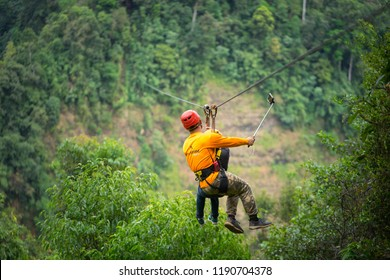 Pakse/Laos - September 2018 ; Zipline' s staff take a traveler playing zipline cross the cliff of Tad Fane waterfall, famous zipline location. He also assist to take selfie photo for the traveler.