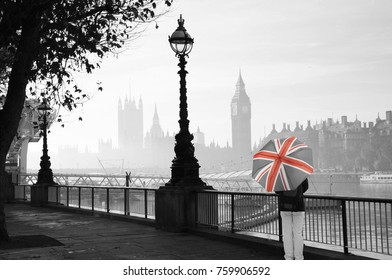 Palace of Westminster in fog seen from South Bank, one  Tourist with Union Jack Umbrella Present
