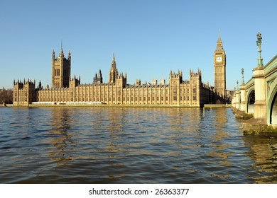 Palace of Westminster, over the Thames, with Big Ben and Westminster Bridge on the right, in golden morning light and a clear blue sky