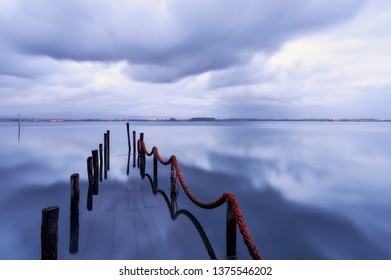 Palafitic pier submerged by the high tide at end of day, only the poles are visible. Blue hour witna tint of orange in the clouds.
