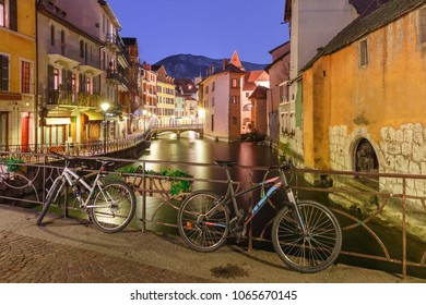The Palais de l'Isle, bridge with bikes and Thiou river during morning blue hour in old city of Annecy, Venice of the Alps, France