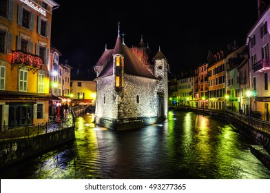 The Palais de l'Isle and Thiou river in Annecy, France at night. Illuminated shops, cafes and restaurants