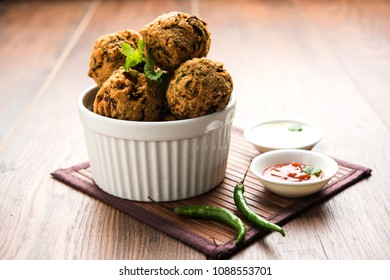 Palak OR Methi Pakora is an Indian Snack served with Green mint chutney and red Sauce, selective focus