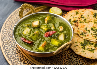 Palak Paneer Curry made up of spinach and cottage cheese, Popular Indian healthy Lunch/Dinner food menu, served in a Karahi with Roti Or Chapati over moody background. selective focus