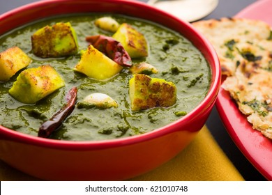 Palak Paneer Curry made up of spinach and cottage cheese, Popular Indian healthy Lunch/Dinner food menu, served in a bowl with Roti Or Chapati over moody background. selective focus
