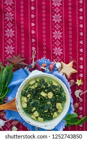 Palak paneer - hot vegetarian traditional Indian food with spinach, cheese, cream gravy, ginger, garlic, garam masala spices. In cast iron skillet pan. Christmas lunch or dinner on red table cloth.