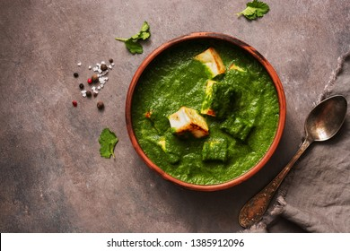 Palak paneer or Spinach and Cottage cheese curry on a dark background. Traditional Indian food. Top view, copy space