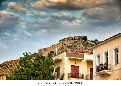 Palamidi fortress up on the hill and hosues on Nafplion city under a dramatic sky