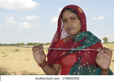 Palana, Bikaner, Rajasthan / India - September 01,2012: Beautiful Rajasthani young girl standing in barbed wireher farm in traditional Rajasthani dress in field