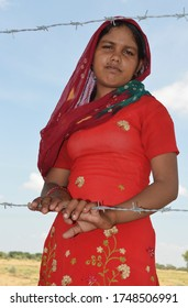 Palana, Bikaner, Rajasthan / India - September 01,2012: Beautiful Rajasthani young girl standing in her farm in traditional Rajasthani dress