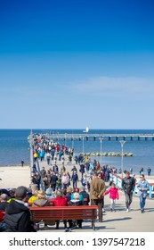 PALANGA, LITHUANIA - APRIL 22, 2019: People walking on the sea bridge. Palanga is a seaside resort town in western Lithuania, on the shores of the Baltic Sea. Summer resort with sand dunes.