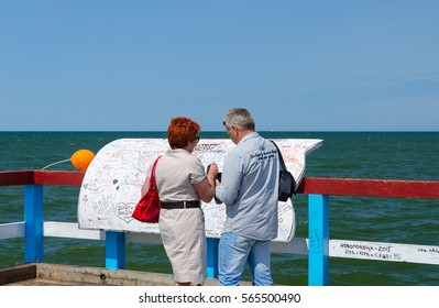 PALANGA, LITHUANIA - JULY 12, 2015: Unidentified tourists leave inscriptions on special board at famous pier in popular resort town of Palanga, Lithuania